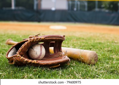 Old baseball, glove, and bat on field with base and outfield in background.