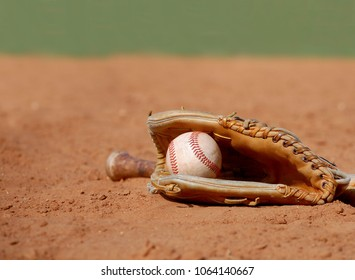 An old baseball glove cradling a worn ball lays in the dusty clay of the infield at a ball park on a sunny day. Shallow depth of field. Copy space.
