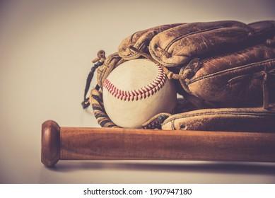 old baseball glove vith ball and bat