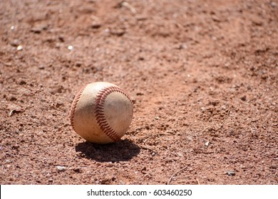 Old baseball with shadow lying in red infield dirt