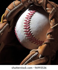 An old baseball sits in a mitt