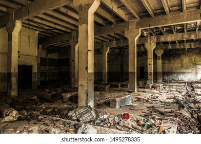 Old basement of abandoned Soviet building. Ruined hall with broken walls and columns. Huge deserted storage of destroyed factory, heavy construction. Creepy scenery, industrial background