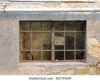 Old basement window set in a crumbling brick and cement wall. The window is closed with rusted metal bars and lock