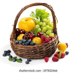 Old basket full of fresh different fruits and berries  with green leaves on a white background