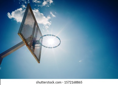 An old basketball basket outside a street with blue sky, copy space for text.