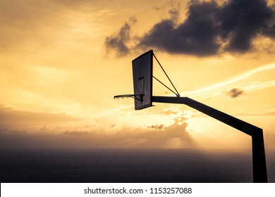 Old basketball board with basket hoop against sunset sky. Sport, recreation.