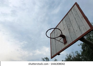 Old basketball Hoop without basket with a blue sky and green trees in the background, bottom view. Wooden Basketball board under cloudy sky in a school yard