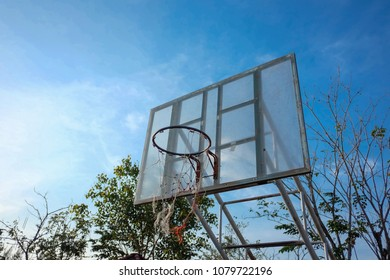 old basketballhoop in the park with blue sky background