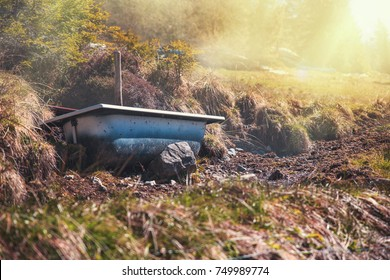 Old bath tub resting on rocks in a meadow in the hills of Germany at sunrise.