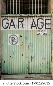 Old battered garage doors. Signs warning about prohibition of parking and evacuation of parked cars. Gzira, Malta.
