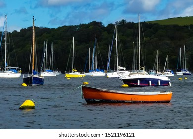 Old, battered orange rowing boat moored to a bright yellow buoy on a tidal estuary. Background of colourful sailing vessels and wooded hillside. Cornwall. England.