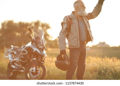 Old bearded Biker standing in front of a motorcycle and looking away outdoors