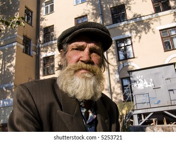 The old bearded man on a urban background