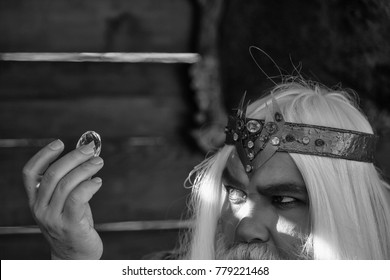 Old bearded man wizard in golden crown with long white hair and beard holding blue gem stone on wooden background