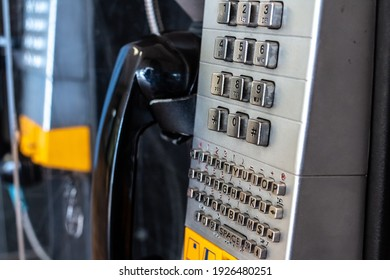 An old beat up payphone at a shopping mall in southwestern Ontario, Canada. Black receiver, yellow credit card slot soft focus. Silver button pad.