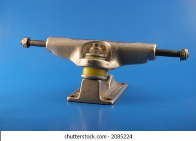 An old beat up skateboard truck sits on a blue background after miles travel and use.