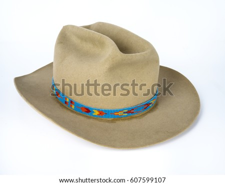 dc17f93e299 Old beat up tan cowboy hat with native american beaded strip on white  background