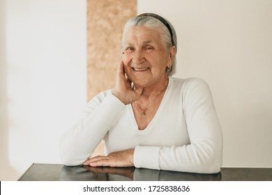 Old beautiful gray-haired woman, grandmother stands happy at home in quarantine. Joy, family, happy life in old age.