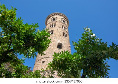 Old beautiful medieval ancient round italian red brick bell tower in Ravenna, summer day with sunlight and blue sky, greenery around