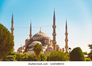 Old and beautiful Ottoman imperial mosque located in Istanbul, Turkey. Blue sky in background and trees in foreground.