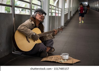 Old beggar or Homeless dirty man singing and playing guitar on footpath of modern city with donate bowl, paper cardboard with help text to beg for money. Poverty in town