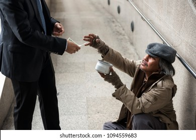 Old beggar or homeless man ask for money while kind Business man pull dollar bill money from suit to donate at city walk in urban town. Poverty and social issue concept. Give and help with sympathy
