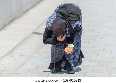 Old beggar woman bent over in a pedestrian zone, Germany