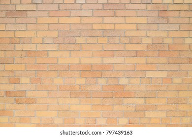Old beige brick wall background texture close up