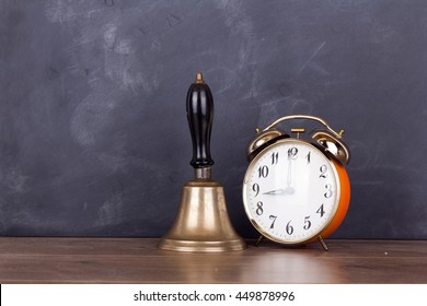 Old bell and alarm clock against a blackboard