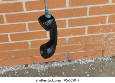 Old Bell Aliant payphone left off the Hook switch at a Barrie plaza with red brick background and loads of salt on the ground.
