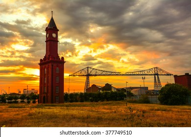 Old Bell Tower and The transporter bridge, Middlesbrough. A gondola carries vehicles across the River Tees above the ships on the river