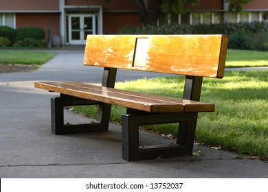 An old bench on at a public university. Its thick wood planks are so smooth and worn with age that they almost glow in late afternoon sunlight.