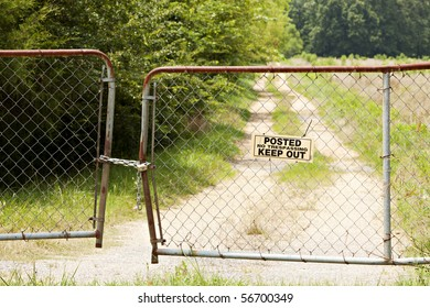 Old bent and rusted fence and gate locked with chain and pad lock with a Posted No Trespassing Keep Out sign