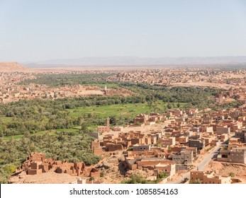 Old Berber village with clay Buildings in Morocco/ Panorama view over oases and Kasbahs and a green river valley