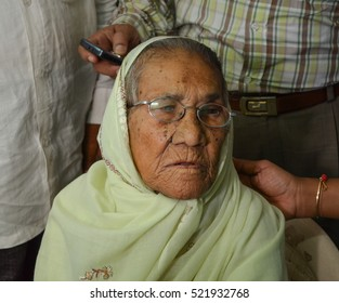 An old bespectacled woman in a burkha covering her head.Image taken at health awareness camp organised by an NGO in Mumbai,India.Image taken on 17/02/2011