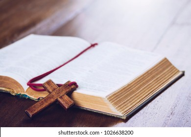 old bible book with  blurred page with wooden cross bookmark  on wooden table, Christian background with copy space