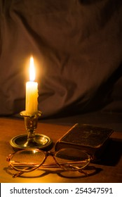 Old bible and candle on a wooden table