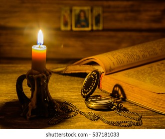 Old Bible and candle on wooden background