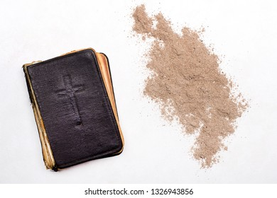 Old Bible, Cross and ash on white background- symbol of Ash Wednesday.