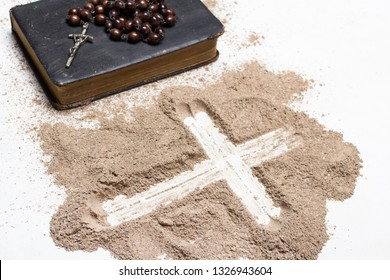 Old Bible, rosary and Cross of ash on white background - symbols of Ash Wednesday.