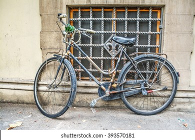old bicycle against a rustic wall in Tuscany, Italy