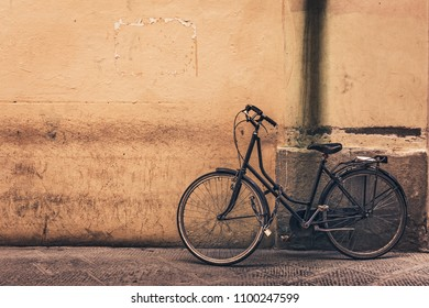 Old bicycle against yellow wall with copy space, toned.