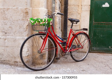 Old bicycle with basket decorated with flowers against a stone wall