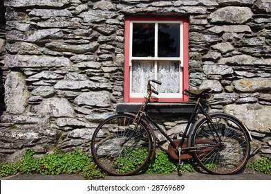 old bicycle by rural cottage wall in ireland. irish old countryside rural home in stone brick wall with window frame red. beautiful irish traditional picturesque postcard type background.