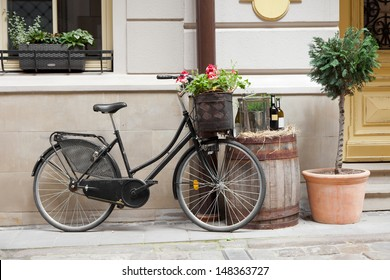 Old bicycle carrying flowers as decoration, wooden barrel with bottles of wine and tree in flower pot