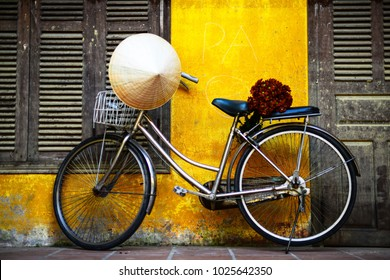 Old bicycle, flower and traditional hat in Hoi An Old Town, Vietnam