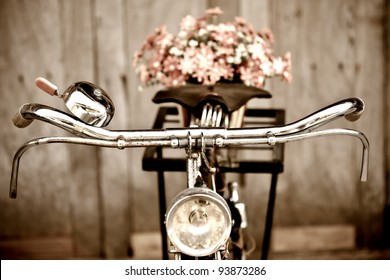 Old bicycle and flowers blur in background process in vintage old style film. Classic design bike with wood wall out focus behind.
