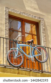 Old bicycle hanging on a balcony of a building in Valencia, Spain - 02/07/2019