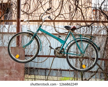 old bicycle hangs on the fence of rustic shed in winter season