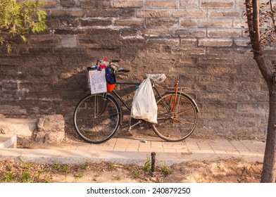 old bicycle is leaning against old brick wall.
